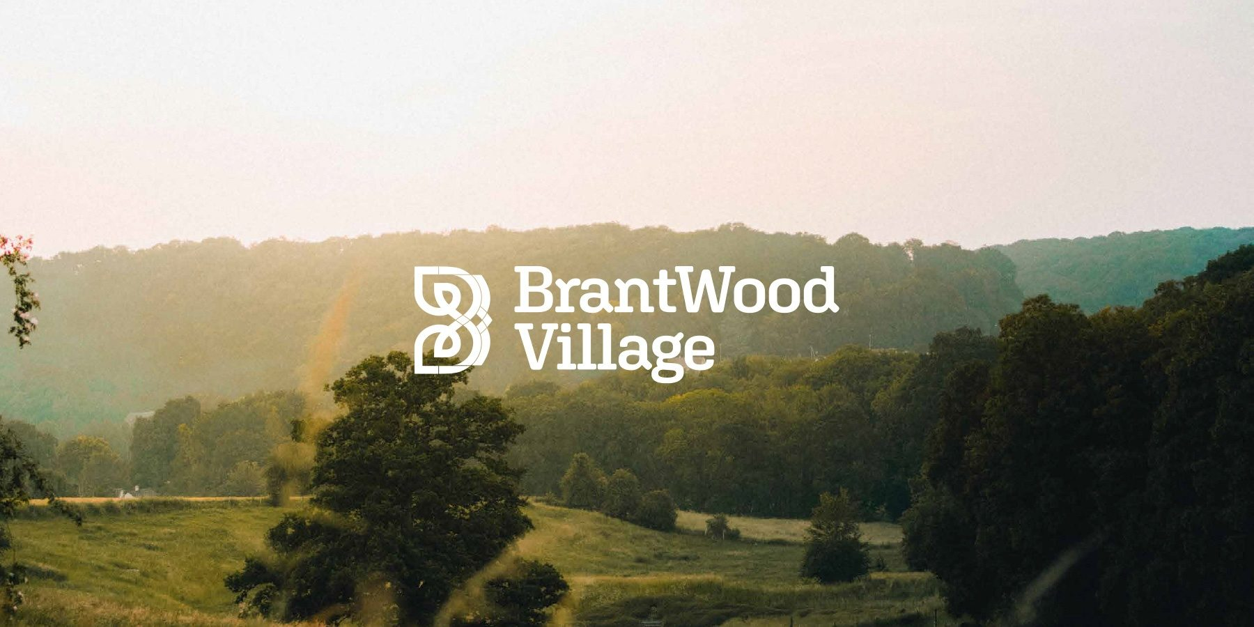 BrantWood Village banner image of a sunset valley with trees